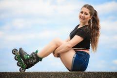 Коньки ролика счастливой молодой женщины нося Стоковые Фото