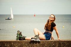 Коньки ролика счастливой молодой женщины нося Стоковые Фотографии RF