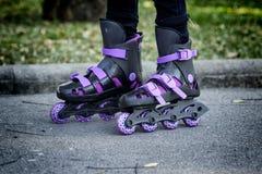 Коньки ролика на красивых ногах ` s девушки Стоковые Фото