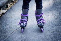 Коньки ролика на красивых ногах ` s девушки Стоковое Изображение
