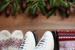 Коньки, свитер и mittens на деревянной предпосылке Стоковое Фото