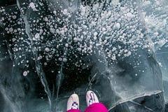 Конькобежец в розовых брюках на красивом льде сказки Lake Baikal и пузырях в льде Стоковая Фотография