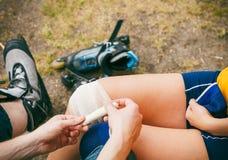 Конькобежец женщины с раненым коленом ноги стоковая фотография