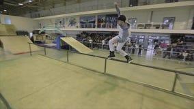 Конькобежец ролика в крышке свертывает на загородке длинного утюга весьма спорт Конкуренция в skatepark смелости сток-видео