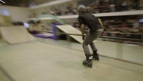 Конькобежец ролика в скольжении шляпы на загородке, кантует смелости Конкуренция в skatepark весьма спорт сток-видео