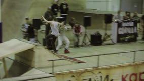Конькобежец ролика делает 180 сальто, нога самосхвата Езда на загородке Конкуренция в skatepark смелости stunt акции видеоматериалы