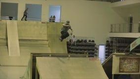 Конькобежец 360 ролика кантует в воздухе, ноге самосхвата трамплин опасно Конкуренция в skatepark сток-видео
