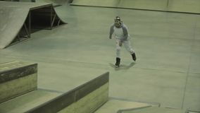 Конькобежец ролика с идет pro на головном сальто на трамплине, езде на загородке Конкуренция в skatepark видеоматериал