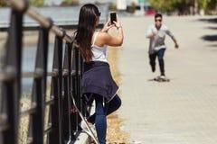 2 конькобежца используя мобильный телефон в улице Стоковое Фото