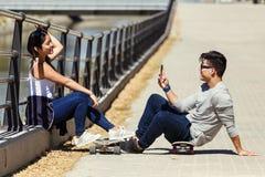 2 конькобежца используя мобильный телефон в улице Стоковое Изображение