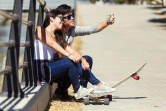 2 конькобежца используя мобильный телефон в улице Стоковая Фотография RF