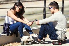 2 конькобежца используя мобильный телефон в улице Стоковые Изображения RF