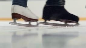 Конькобежцы катаясь на коньках на тормозах льда
