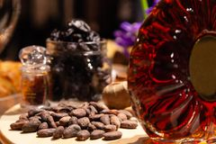 Коньяк или рябиновка крупного плана роскошные в кристаллической круглой бутылке с гайками, закусками, черносливами Дегустация кон стоковое изображение