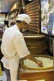 Кондитер изготовляет печенья в магазине конфеты Стоковое фото RF