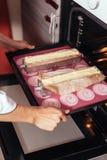 Кондитер кладет печенье в печь Стоковые Фотографии RF