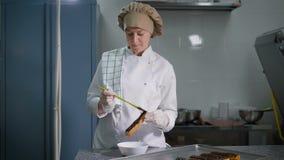 Кондитер нежно мажет толстый шоколад слоя на свеже испеченных eclairs Профессиональный шеф-повар во время ее любимой работы акции видеоматериалы