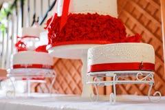 Кондитер украшая свадебный пирог с цветками марципана стоковое изображение