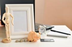 Копилка и деньги, кредитная карточка, часы, рамка, тетрадь и деревянная диаграмма человека на предпосылке ноутбука дальше стоковое изображение rf