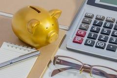 Копилка свиньи, калькулятор, телефон, тетрадь, ручка, стекла, концепция денег сбережений стоковое изображение rf