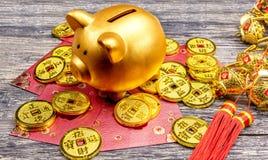 Копилка с золотыми монетками, красными конвертами и китайским орнаментом на деревянном столе стоковое изображение