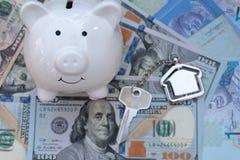 Копилка улыбки с домашней ключевой цепью на предпосылке доллара США Сбережения для концепции вклада свойства стоковое изображение