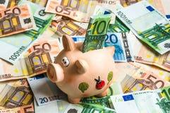 Копилка в куче денег евро Стоковые Изображения