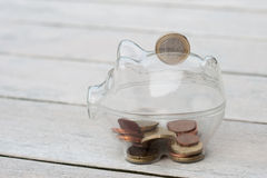 Копилка, при монетки падая в шлиц. Стоковое Изображение