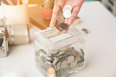 Копилка при рука держа монетку денег Стоковые Фотографии RF