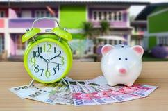 Копилка с деньгами и будильником на деревянной таблице и на доме Стоковое Фото