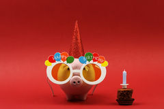 Копилка с солнечными очками с днем рождения, шляпой партии и именниным пирогом с свечой на красной предпосылке Стоковые Изображения