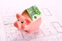 Копилка с 100 счетами евро как крыша на чертеже дома Стоковая Фотография RF