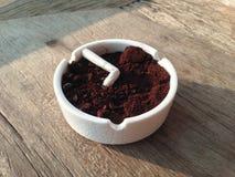Копченая сигарета в белом Ashtray на таблице Стоковая Фотография RF