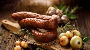 Копченая сосиска на деревянной деревенской таблице с добавлением свежих ароматичных трав и специй стоковые изображения rf