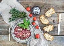 Копченое мясо в винтажной серебряной плите с свежими базиликом, вишн-томатами и кусками хлеба над деревенской древесиной Стоковое фото RF