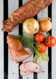 Копченое мясо, который служат с томатами и луками Поясницы свинины Яблока деревянные копченые Отрезанные мясо и овощи стоковые фото