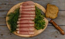 Копченые ветчина, базилик, укроп, хлеб и нож на деревянной плите Стоковые Изображения