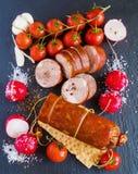 Копченые сосиска и овощи (томаты вишни, редиска и чеснок) на черной каменной предпосылке Взгляд сверху Стоковое Изображение