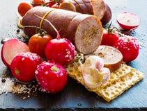 Копченые сосиска и овощи (томаты вишни, редиска и чеснок) на черной каменной предпосылке Стоковое Изображение