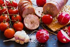 Копченые сосиска и овощи (томаты вишни, редиска и чеснок) на черной каменной предпосылке Стоковая Фотография RF