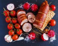 Копченые сосиска и овощи (томаты вишни, редиска и чеснок) на черной каменной предпосылке Взгляд сверху Стоковая Фотография