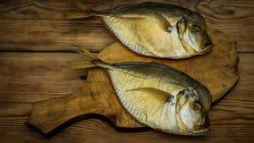 2 копченых рыбы на деревянной разделочной доске Стоковое фото RF