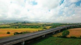 Корабли управляют вдоль шоссе между желтыми и зелеными полями и сельскими поселениями к день лета пасмурный в Тоскане, Италии акции видеоматериалы