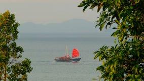 Корабль традиционного китайския с красными ветрилами плавает вдоль моря на заходе солнца акции видеоматериалы