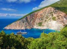 Корабль шлюпки флибустьера пирата с туристами на сини Закинфа выдалбливает залива моря пляжа Sparto ликования Утесы влажного песк Стоковые Изображения RF