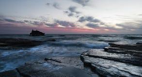 Кораблекрушение покинутого корабля на скалистом береге Стоковые Фото