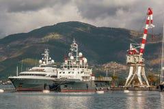 Корабль и кран на козлах огня на предпосылке гор Стоковое Фото