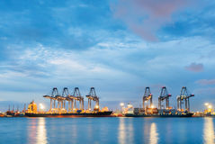 Корабль перевозки груза контейнера с работая мостом крана в верфи на сумраке для логистического экспорта импорта Стоковые Фото