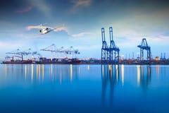Корабль перевозки порта груза контейнера с работая мостом крана в верфи на сумраке для логистической предпосылки экспорта импорта Стоковая Фотография RF