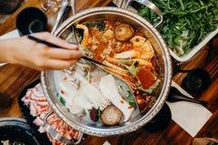 Корейская горячая еда бака Руки принимая еду с палочками Стоковые Фотографии RF
